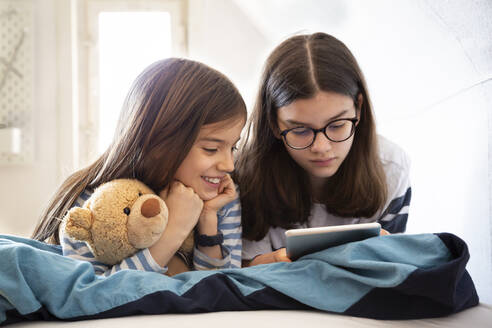 Sisters using tablet lying on bed - LVF08848