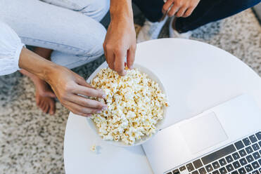 Low section of couple having popcorn by laptop at table in house - KIJF02979
