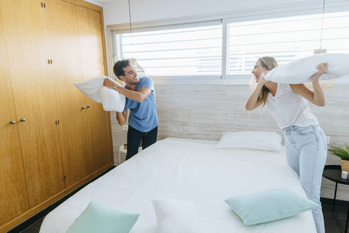 Happy carefree couple having pillow fight in bedroom at home - KIJF02985