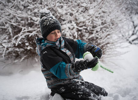 Young boy making snowball with snowball making toy on winter day. - CAVF79315