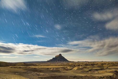 Star trails over badlands and Factory Butte, Upper Blue Hills, Utah - CAVF79348