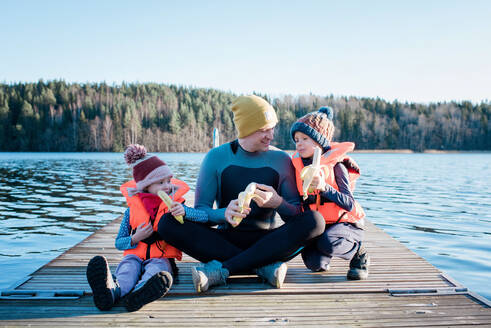 Dad sat on a jetty in a wetsuit eating fruit with his kids by a beach - CAVF79381