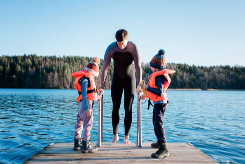 Father and his children cold water swimming at the beach in Sweden - CAVF79387