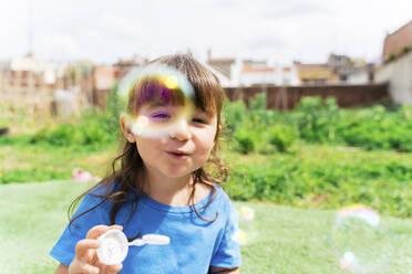 Portrait of happy little girl blowing soap bubbles in a park - GEMF03605