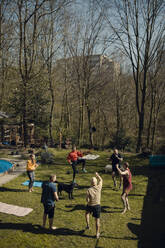Group of friends doing workout together in garden - GUSF03594