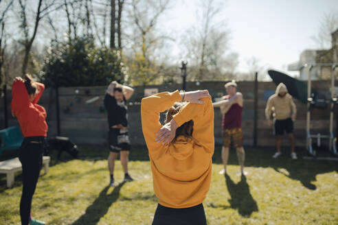 Group of friends doing workout together in garden - GUSF03597