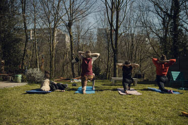 Group of friends doing workout together in garden - GUSF03600
