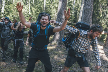 Young people backpacking in nature, laughing and waving at camera - GUSF03696