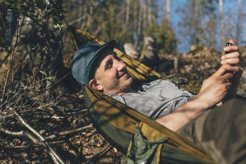 Young man relaxing in hammock, using smartphone - GUSF03699