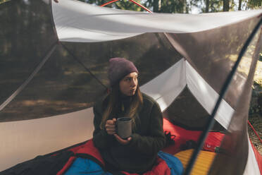 Young woman in tent isn the forest, drinking tea - GUSF03705