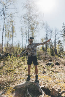 Young man gaming with VR glasses in the forest - GUSF03735