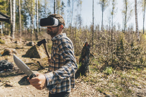 Young man gaming with VR glasses in the forest, holding axe and knife - GUSF03738