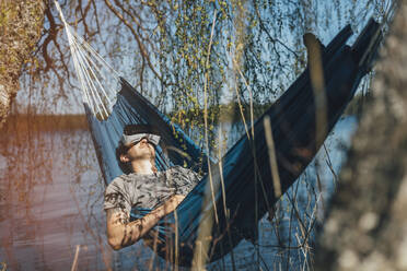 Young man relaxing in hammock, using VR glasses - GUSF03741