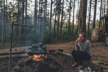 Young woman resting at camp fire, drinking tea - GUSF03756