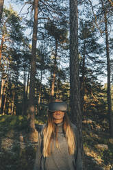 Young woman using VR goggles in nature - GUSF03765