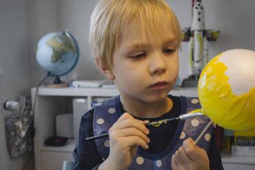 Portrait of little boy painting ball yellow - JOSEF00320