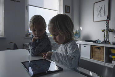 Little girl testing digital tablet while her older brother watching her - JOSEF00323