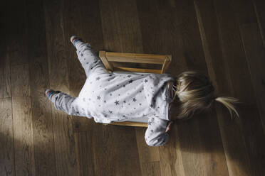 Back view of toddler girl lying on chair, top view - JOSEF00326