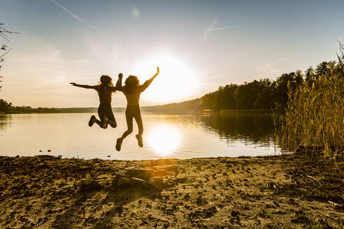 Friends jumping in mid-air at lakeshore against sky during sunset - OJF00391