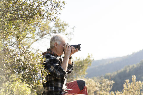 Senior man photographing in nature - AFVF06127