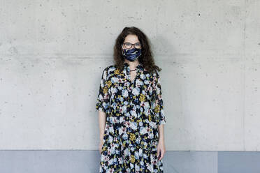 Woman wearing homemade mask in front of a wall - FLLF00450