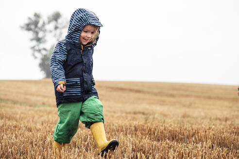 Happy little girl walking on stubble field at rainy day - WFF00372