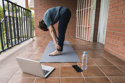 Senior woman practising yoga with laptop on balcony - XLGF00066