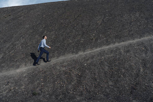 Mature businessman walking up a disused mine tip - JOSEF00388