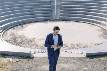 Mature businessman using tablet at an amphitheatre on a disused mine tip site - JOSEF00397