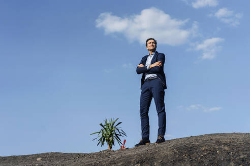 Confident mature businessman standing on a disused mine tip next to a plant - JOSEF00412