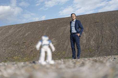 Businessman and miniature robot on a disused mine tip - JOSEF00415