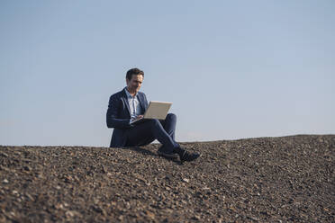 Mature businessman using laptop on a disused mine tip - JOSEF00427