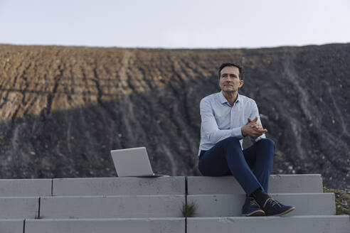 Mature businessman sitting on stairs on a disused mine tip next to laptop - JOSEF00451