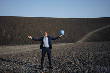 Mature businessman holding a globe on a disused mine tip - JOSEF00466