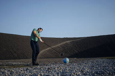 Mature man with a mask playing golf with a globe on a disused mine tip - JOSEF00469