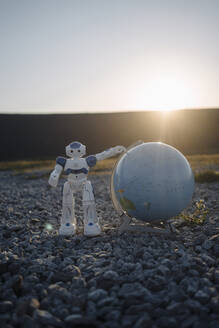 Mini robot with globe on a disused mine tip at sunset - JOSEF00472