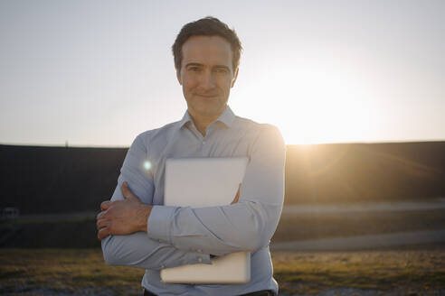 Portrait of mature businessman holding laptop on a disused mine tip at sunset - JOSEF00475