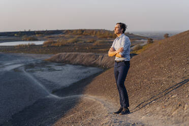 Mature businessman standing on a disused mine tip looking at view - JOSEF00484