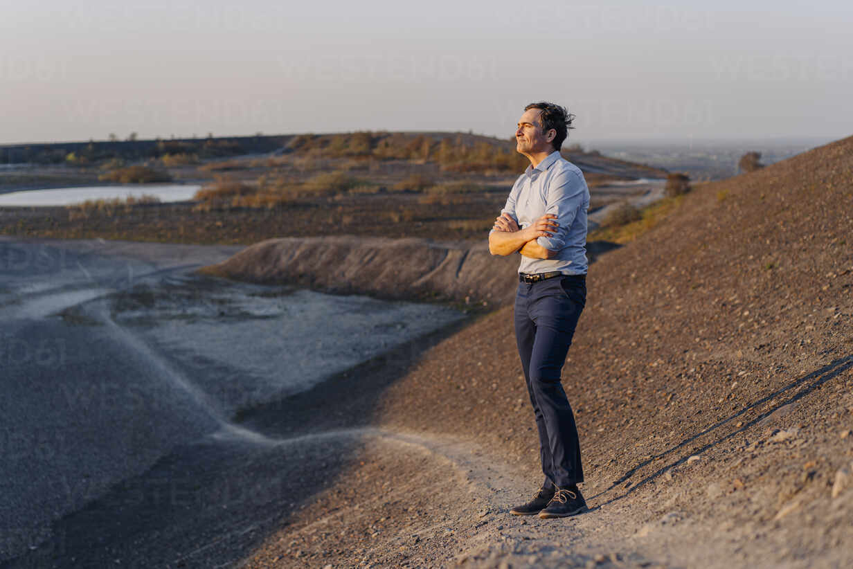 Mature businessman standing on a disused mine tip looking at view - JOSEF00484 - Joseffson/Westend61