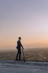 Mature businessman riding a kick scooter on a disused mine tip at sunset - JOSEF00490