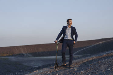 Mature businessman with a kick scooter on a disused mine tip at sunset - JOSEF00493