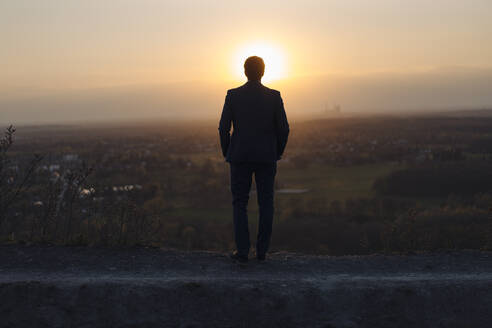 Mature businessman standing on a disused mine tip at sunset looking at view - JOSEF00496