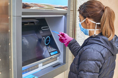 Woman wearing mask using credit card at ATM during pandemic situation - VEGF01973