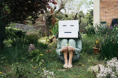 Young woman with cardboard box on her head sitting barefoot in garden - AFVF06131