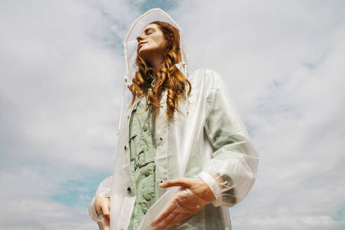 Redheaded young woman with eyes closed wearing transparent rain coat standing against sky - AFVF06140