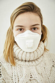 Portrait of blond woman wearing FFP2 mask at home - FSF01033