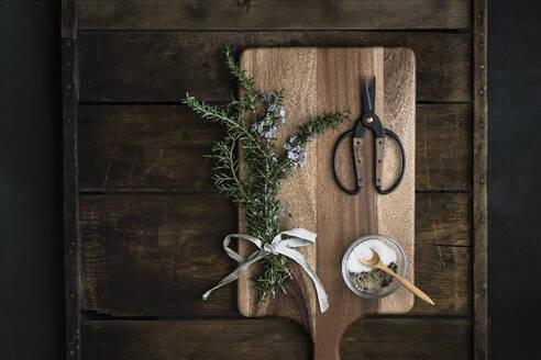 Bundle of fresh rosemary, coarse salt, scissors on cutting boards - CAVF80291