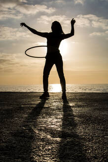 Happy woman playing with hula hoop at harbour during sunset - XLGF00084