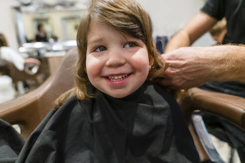 Portrait of smiling little girl getting haircut - MGIF00903