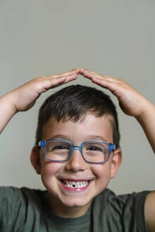 Portrait of little boy with tooth gap wearing blue glasses - MGIF00909